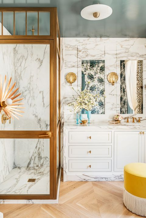 a fancy bathroom with white marble, a teal ceiling, white cabinets, gold touches and quirky lamps is a chic and lovely space