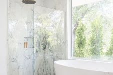 a fancy bathroom with white marble in the shower space, a glazed wall, a bathtub, a coral ottoman and a gold sunburst chandelier