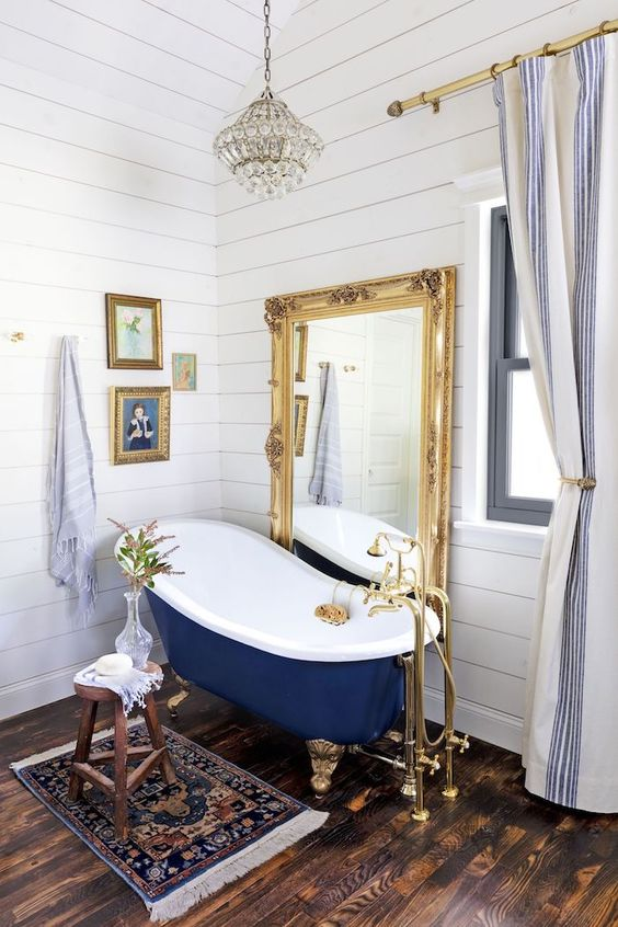 a fancy bathroom with white planked walls, a dark stained floor, a vintage navy bathtub, a floor mirror in a gilded frame, a mini gallery wall and a crystal pendant lamp