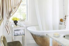 a fancy bathroom with white planked walls and a floor, a vintage bathtub, vintage and refined furniture, a striped curtain looks wow