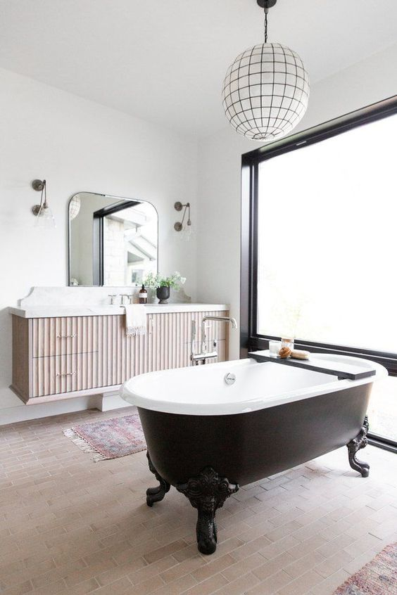 a fancy bathroom with white walls and a neutral tiled floor, a black vintage bathtub, a floating vanity and a pendant lamp plus a frosted glass wall
