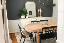 a farmhouse dining room with a grey accent wall, a vintage wooden dining table, black chairs and a bench, a vintage chandelier and a sideboard with some decor