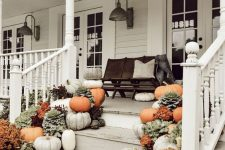 a farmhouse fall porch with a black bench and lots of pillows, pumpkins, blooms and greenery and vintage sconces on the walls