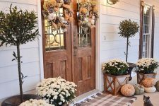 a farmhouse fall porch with plaid rugs, potted blooms, heriloom pumpkins, potted trees and feather wreaths plus wall lanterns