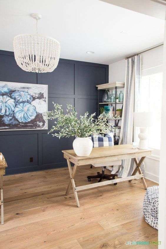 a farmhouse home office with a navy paneled wall, a trestle desk, a shelving unit, a beaded chandelier and a bold artwork