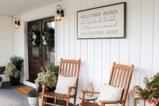 a farmhouse porch styled for summer, with wooden rockers, potted plants, a sign and a rug is a very welcoming and cool space