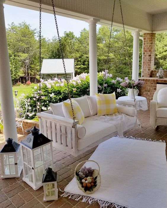 a farmhouse porch with a white upohlstered bench on chains, several candle lanterns, a white wicker chair and some pretty textiles to cozy up the space