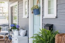 a farmhouse porch with a wicker chair and printed textiles, a suspended bench, layered rugs, a sideboard and a watering can plus blooms and greenery