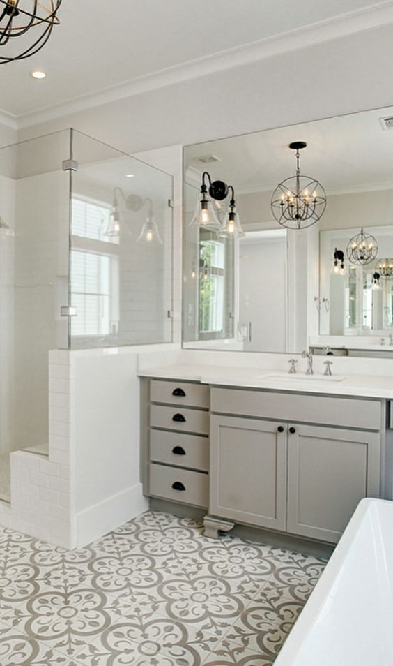 a gorgeous modern country bathroom with a grey and white mosaic tile floor, grey furniture, white appliances, a shower space and cool vintage lamps