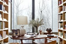 a gorgeous modern country home office with shelving units, a desk, a woven chair, a glazed wall for a lovely view and some wooden accessories