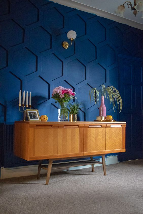 a gorgeous navy hexagon panel accent wall, a stained vintage dresser, some greenery and blooms and elegant candles in a candle holder