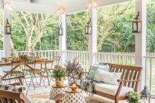a large and welcoming farmhouse porch with a simple wooden dining set, wooden benches with upholstery, side tables and potted plants