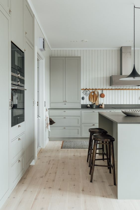 a light grey modern country kitchen with shaker style cabinetry, black countertops and built-in appliances, a modern hood and tall stools