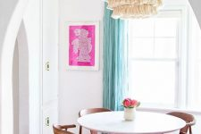 a lovely and airy dining space with a round table, hot pink chairs, a pink printed rug, a tassel chandelier and a hot pink artwork