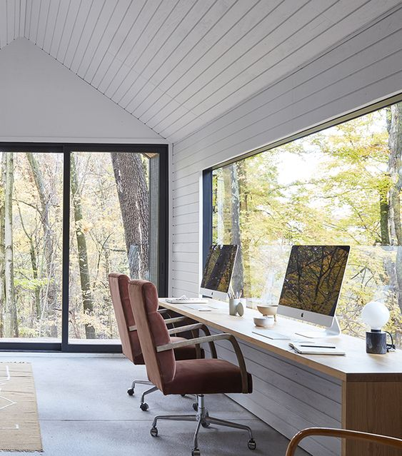 a lovely and clean shared modern country home office with white planked walls and a shared desk plus glazed walls for views
