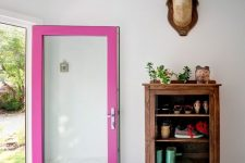 a lovely and quirky entryway with a mosaic tile floor, a vintage wooden cabinet, a door with a hot pink frame and taxidermy