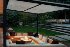 a lovely and welcoming contemporary conversation pit with a fire pit, built-in upholstered benches and pillows around