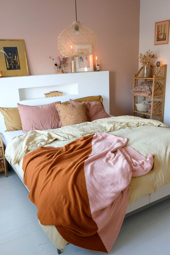 a lovely bedroom with a pink accent wall, a bed with an accent headboard, a pendant lamp and pretty bedding, a woven shelf and some artworks