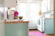a light blue and white kitchen design with a pink rug