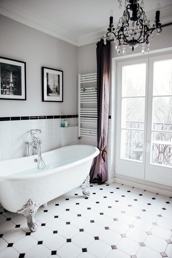a lovely fancy bathroom with a black and white mosaic tile floor and tiles on the wall, a chic bathtub, purple curtains, a crystal chandelier