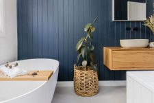 a lovely modern country bathroom wiht a navy planked accent wall, a floating vanity, white appliances and a woven lamp and a planter is great