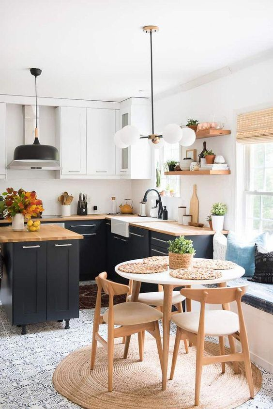 a lovely modern country kitchen with white and navy cabinets, butcherblock countertops, pendant lamps and black fixtures