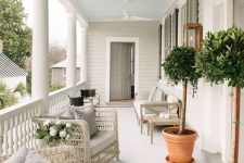 a lovely modern farmhouse porch with neutral wicker furniture, an upholstered bench and chairs, potted trees and lanterns