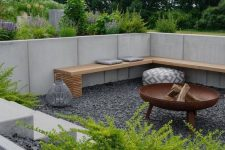 a lovely modern sunken patio with gravel on the ground, a bench and a fire pit plus greenery growing around to refresh the look