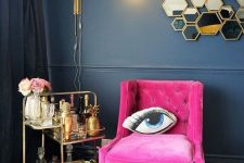 a lovely nook with a navy wall and black curtains, a hot pink chair, a gold bar cart, a cool gold sconce and hexagon mirrors