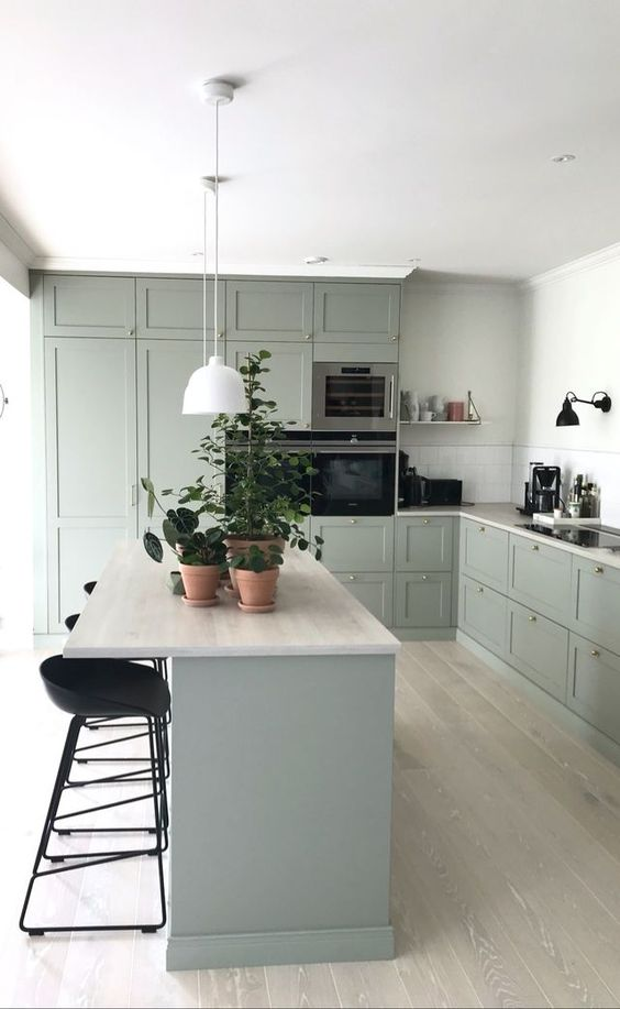 a lovely pale green modenr country kitchen with neutral countertops and tall black stools and sconces is a chic room