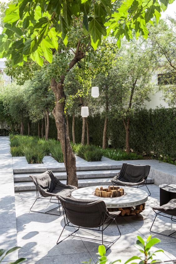 a lovely sunken outdoor space fully clad with tiles, with a round fire pit, some upholstered chairs and a living wall