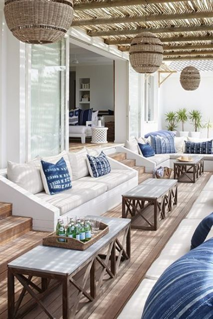 a lovely sunken patio with built in upholstered benches, coffee tables and woven pendant lamps attached to the roof