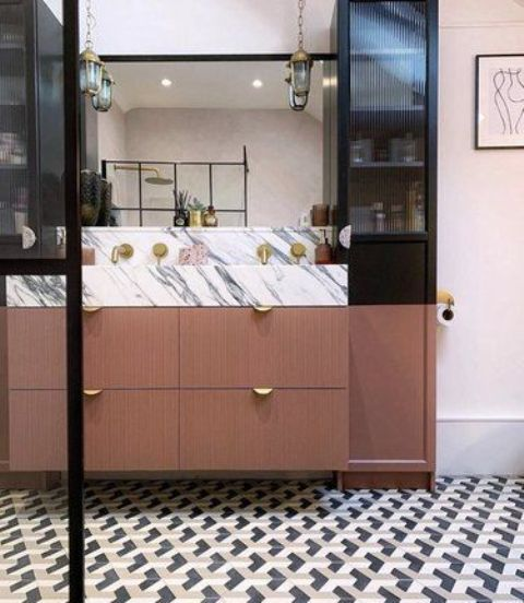 a luxurious bathroom with a geometric tile floor, a lovely vanity with a white marble countertop, gold touches and pendant lamps on chains