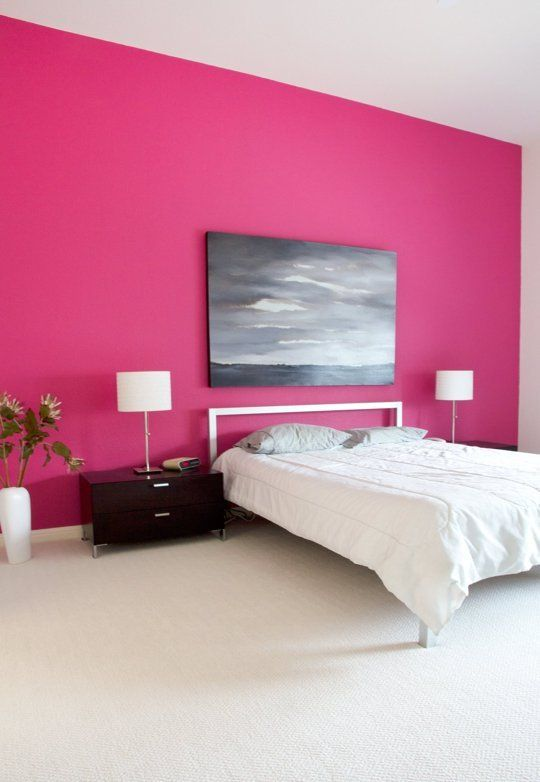 a minimal bedroom with a hot pink accent wall, a white bed, black nightstands, a statement artwork and some white lamps