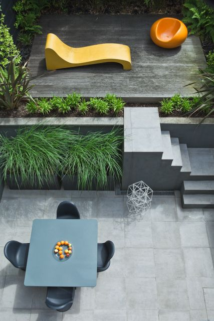 a minimalist outdoor space with a raised platform with a lounger and a fire pit and a dining space plus growing grasses around