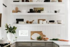 a modern English country kitchen with white planked walls, grey shaker style cabinets, open shelves, gold touches and potted plants