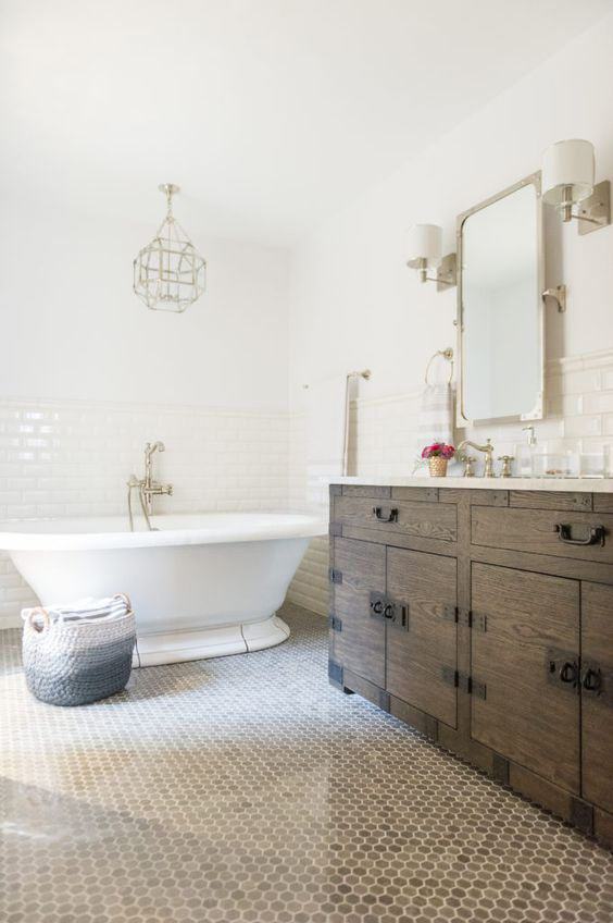 a modern French country bathroom with subway and penny tiles, a stained vanity, a vintage tub and a faceted lamp plus gold touches