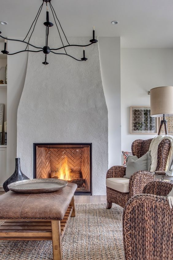a modern French country living room with a large fireplace, a leather ottoman as a table, woven chairs and a jute rugs looks unique