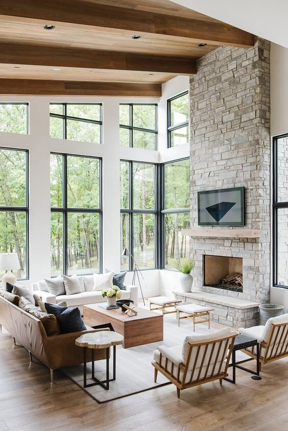 a modern Provence style living room with a fireplace clad with stone, chic neutral furniture, stools and coffee tables