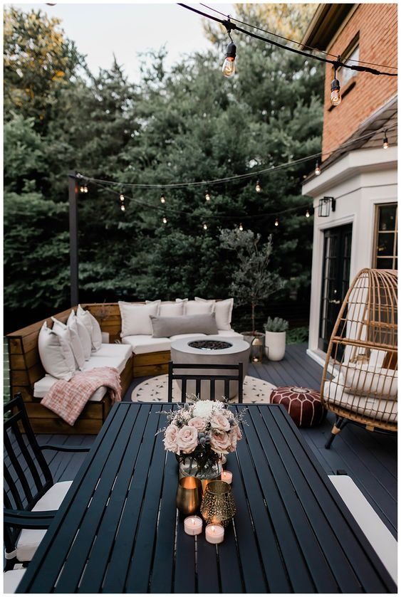 a modern and bold farmhouse terrace with a black deck, a built-in bench with upholstery, a rattan egg chair, a black planked dining set