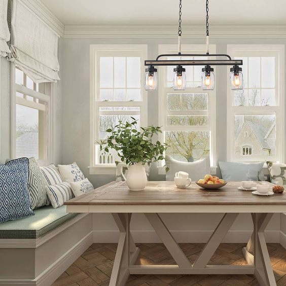 a modern coastal dining space with a built-in banquette seating, a stained trestle dining table, a vintage chandelier and printed pillows