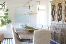 a modern coastal farmhouse dining room with a stained buffet, a stained table, upholstered chairs, a modern chandelier