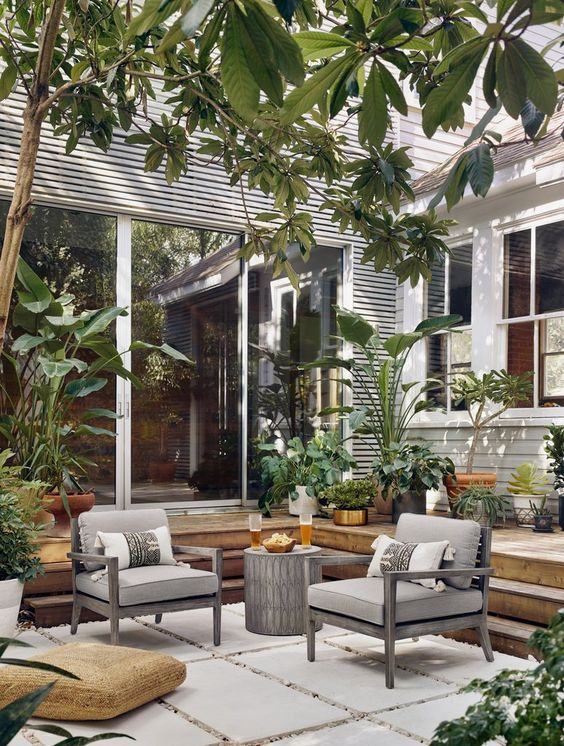 a modern country backyard with a wooden deck and clad with tiles, with comfy chairs, a side table, a jute pouf, potted plants and trees