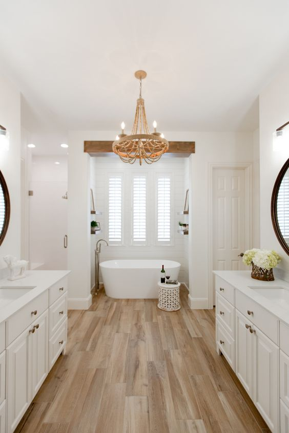 a modern country bathroom with a laminate floor, white walls, elegant white shaker style vanities and cool white appliances plus a wooden chandelier