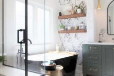 a modern country bathroom with a mosaic tile floor and a wallpaper accent wall, a shower and a black bathtub, a green vanity and potted plants