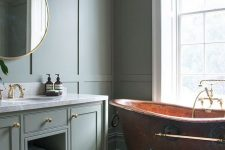 a modern country bathroom with grey green paneled walls and a matching vanity, a copper vintage bathtub and a lovely mosaic tile floor