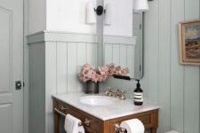 a modern country bathroom with pale aqua paneling, a stained vanity, white appliances, vintage lamps and some blooms