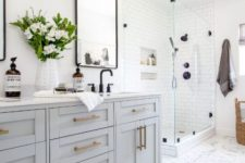a modern country bathroom with white marble herringbone tiles, white subway ones, a light grey vanity and a shower space plus brass touches