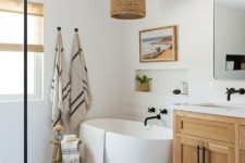 a modern country bathroom with white mismatching tiles, a stained vanity, white appliances, black fixtures and a woven lampshade