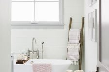 a modern country bathroom with white planked walls, a grey tile floor, white appliances, rough wooden accessories is cool